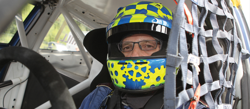 Derek Tohill in his racing car with branded helmet